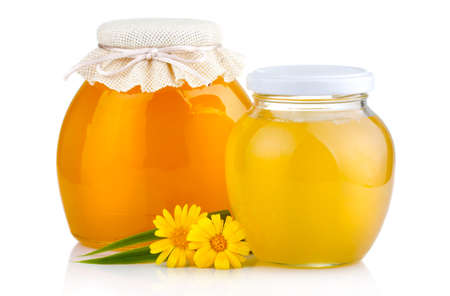 Sweet honey in glass jars with flowers isolated on white background  photo