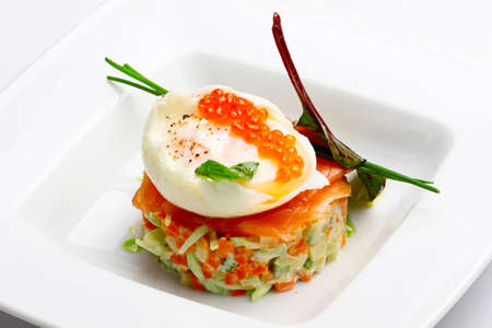 Russian salad with salmon and red caviar on wight background photo