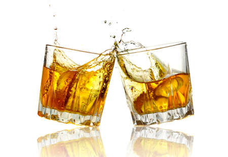 Two whiskey glasses clinking together, isolated on white. photo
