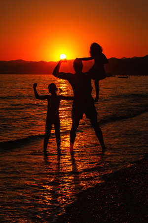 Happy family silhouettes over sunset on the Mediterranean Sea. 스톡 콘텐츠