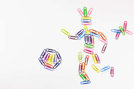 the football player is made of colorful office paper clips and hits the ball on a white background. Pink crimson, blue, purple memo paper clips.Plastic paper clips background