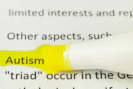 macro photography of the word autism from the newspaper underlined with red and yellow markers