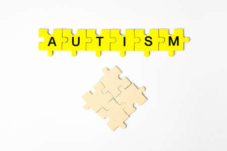 autism, concept the word autism is made up of puzzles in yellow with black letters on a white isolated background Archivio Fotografico