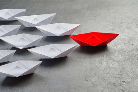 Business Concept, Paper Boat, the key opinion Leader, the concept of influence. One red paper boat as the Leader, leading in the direction of the white ships on a gray concrete background