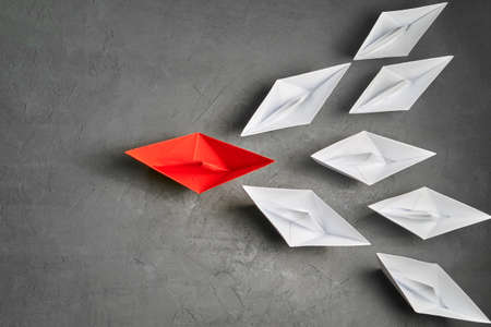 Business Concept, Paper Boat, the key opinion Leader, the concept of influence. One red paper boat as the Leader, leading in the direction of the white ships on a gray concrete background,flat lay,copy space Stockfoto