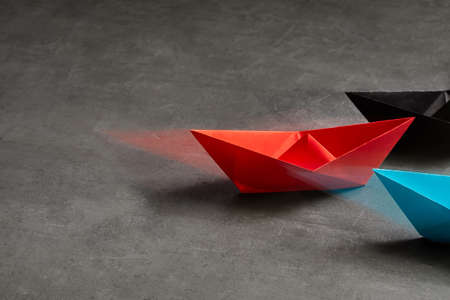 Business Concept, Paper Boat, the key opinion Leader, the concept of influence.Red.blue and black paper boat as the Leader on a gray concrete background,copy space