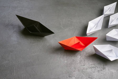 Opportunities Business Concept-Paper Boat key opinion Leader, influence concept. One black paper boat as a Leader, leading in the direction of the white ships goes to meet the red paper boat which leads the white ships on a gray concrete background, shows how the meeting of two businessmen on the same site