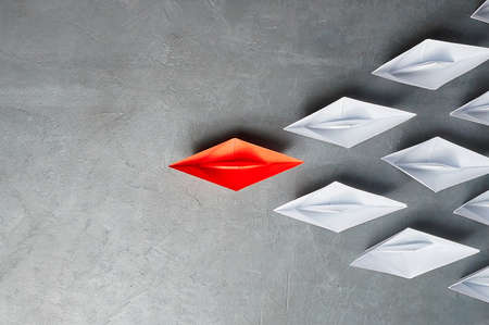 Business Concept, Paper Boat, the key opinion Leader, the concept of influence. One red paper boat as the Leader, leading in the direction of the white ships on a gray concrete background,copy space,flat lay