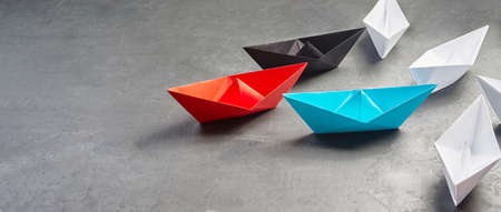 Business Concept, Paper Boat, the key opinion Leader, the concept of influence.Red,blue and black paper boat as the Leader, leading in the direction of the white ships on a gray concrete background,copy space Zdjęcie Seryjne