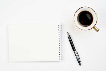 Vista superior del escritorio de oficina blanco con Bloc de notas, bolígrafo y taza de café, diseño minimalista, vista superior, espacio de copia, endecha plana