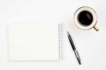 white office Desk top view with Notepad, pen and coffee Cup, minimalistic design, top view,copy space,flat lay