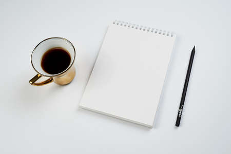 white office Desk top view with Notepad, pencil and coffee Cup, minimalistic design, top view,copy space,flat lay Stockfoto