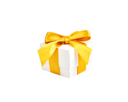 Handmade white paper box with yellow gold satin ribbon and bow on an isolated white background Foto de archivo - 138472463