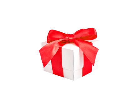 Handmade white paper box with red satin ribbon and bow on an isolated white background Foto de archivo - 138472511