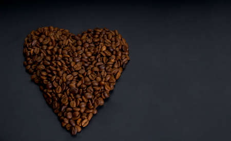 Roasted arabica coffee beans laid out in the shape of a heart, lie on a dark wooden background close up