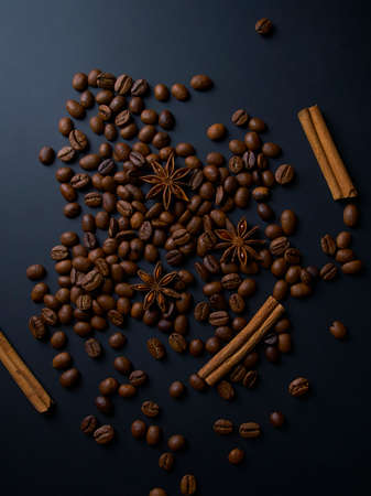 Roasted arabica coffee beans, cinnamon sticks and anise stars on a dark wooden background,top view Foto de archivo