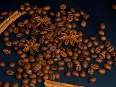 Roasted arabica coffee beans, cinnamon sticks and anise stars on a dark wooden background,close-up