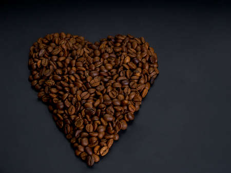 Roasted arabica coffee beans laid out in the shape of a heart, lie on a dark wooden background close up,copy space