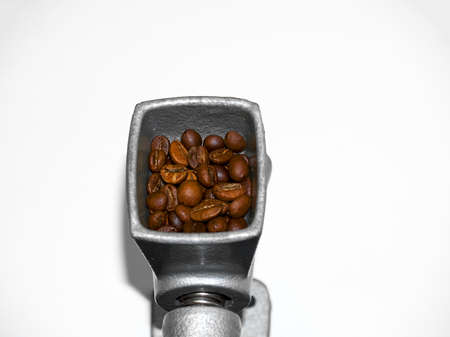 Vintage antique manual coffee grinder with roasted coffee beans, ground coffee on wooden table,top view
