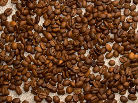 Roasted coffee beans scattered on a burlap napkin.coffee background