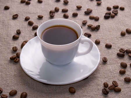 A white espresso cup stands on a burlap table with scattered coffee beans.