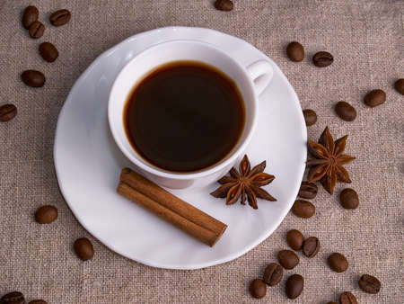 A white cup of espresso stands on a burlap table with scattered coffee beans, a cinnamon stick and stars of anise.