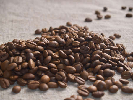 Roasted coffee beans scattered on a burlap napkin. Foto de archivo