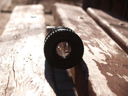 close up photo of old camera lens over wooden table. image is retro filtered. selective focus Foto de archivo
