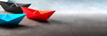 Red blue and black paper origami boats lie on concrete background. teamwork concept Foto de archivo