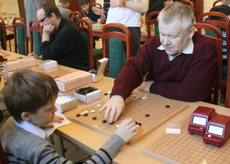 competitividad: SAINT PETERSBURG, RUSSIA - Jan 29, 2012. Chinese New Year Go Game Tournament. Valery Shikshin (go coach) is teaching young boy to play go on the competition during the break.