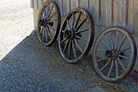 to tinker: old wooden cart wheel in a garden Stock Photo
