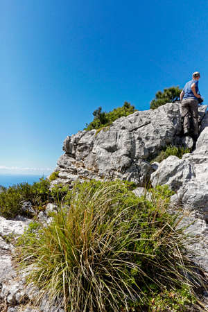 a hiker top of the hill on a sunny day with blue sky, Mallorca, Europe