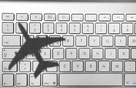 Airplane shadow on a computer keyboard Stock Photo - 8572785