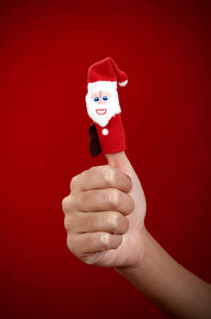 Christmas finger puppet on red background photo