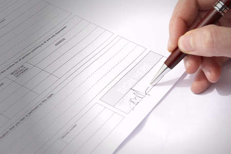 hand that signs a document photo