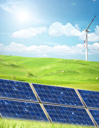 Alternative energy in a green field on a sky background photo