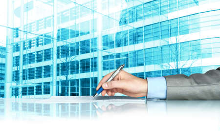 Businessman signing contract against modern offices photo