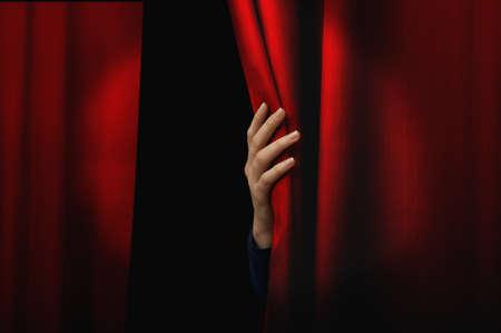 Meisje opent een rood gordijn