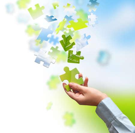 Pièce d'un puzzle vert à la main