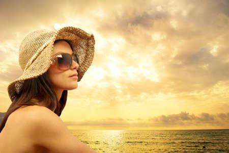 puesta de sol: Chica sexy en la playa durante la puesta de sol