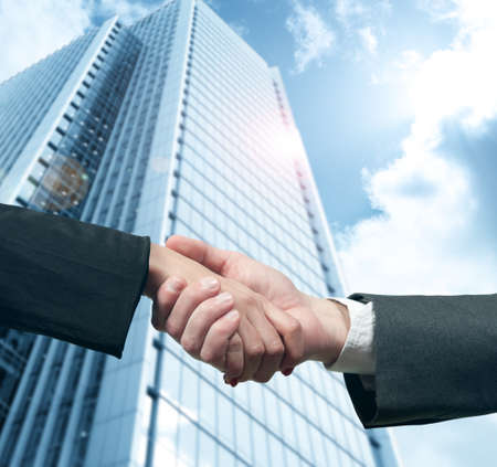 business  deal: Business handshake with modern office skyscraper