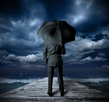 financial crisis: Businessman with umbrella against the storm Stock Photo