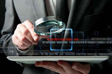 security search: Businessman looks for the malicious code of a virus Stock Photo
