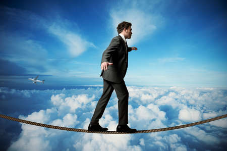 risky business: Businessman is balancing on a rope