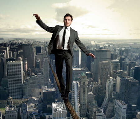 risky job: Businessman is balancing on a rope