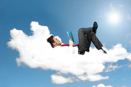 Kaufmann liest in einem Buch auf einer Wolke