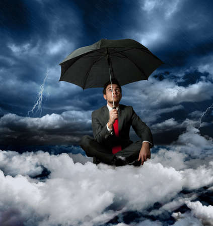Businessman on a cloud during a storm Stock Photo - 13422934