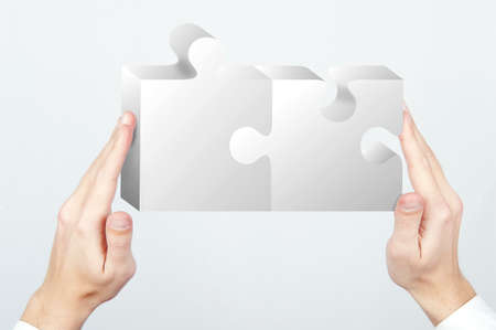 Businessman holding two pieces of a puzzle Stock Photo - 13618037