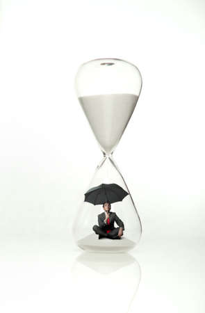 Businessman is protected from the time of the hourglass photo