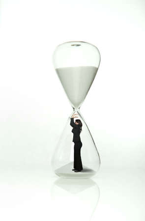 Businesswoman stops time from the hourglass photo